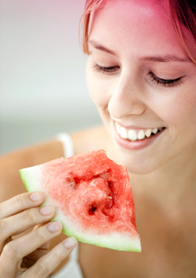 Bilde av en ung kvinne som spiser vannmelon. Bildet viser en av tipsene for å lindre menstruasjonssmerter - spis frukt eller grønnsaker som inneholder mye vann.