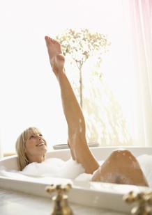 Bilde av en kvinne i et badekar med et utstrakt ben. Bildet viser, at det går an å slappe av og leve som vanlig, også under menstruasjonen din.