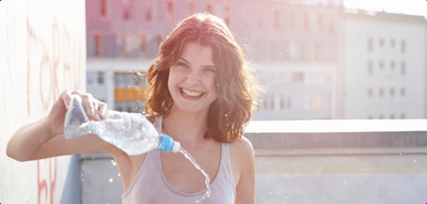 Bilde av en ung smilende kvinne som holder en vannflaske i hånden og spruter vann.